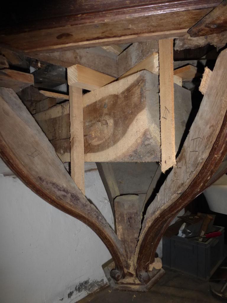 De onderkant van de preekstoel. Hier zie je hoe hij met klossen is rechtgezet.